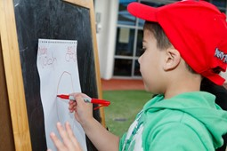 Little boy wearing a red cap and green hoodie drawing on a paper stuck on a board with red pen