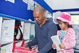 Father with his daughter in pink jacket and hat collecting her bag and other things at child care