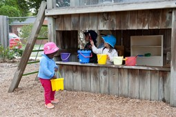 Two children with play equipments at child care
