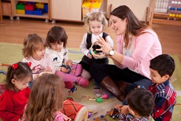 Children and female child care educator sitting in a circle and playing with toys that produce sound
