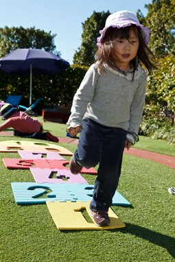Young girl playing hop, skip, jump on number play mats in an outdoor environment at child care