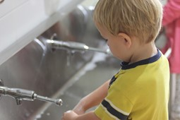 little boy in yellow t-shirt washing hands at child care