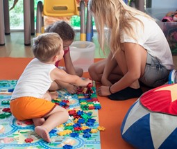 Child care educator playing with two children