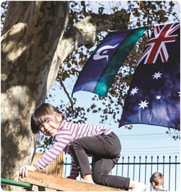 Child on play equipment with flags in background