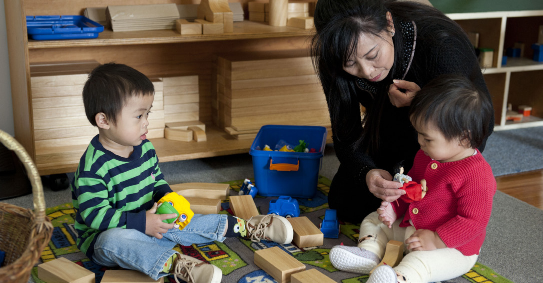 Female educator and two children playing with wooden blocks