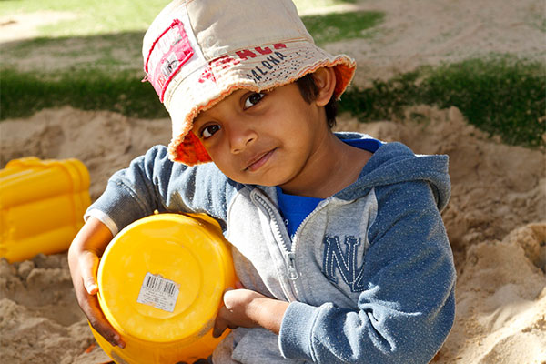 Young boy playing with bucket in sandpit