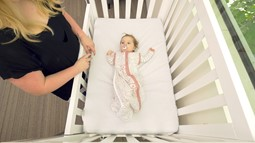 educators puts baby down in a cot