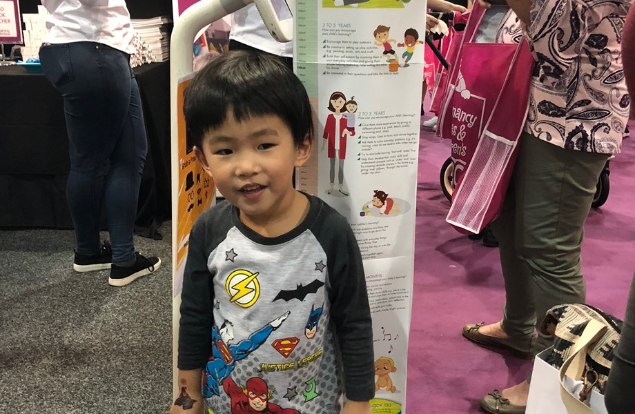 a child standing against height chart at a parenting expo