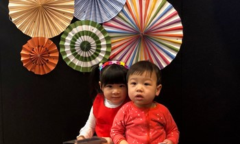 Two little children photographed against a wall with paper fans decor
