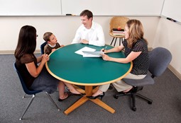 An educator sitting at a round table with a child and their parents