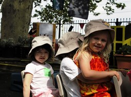 Three children in outdoor play space in hats sitting in chairs. One child is sitting on the lap of another