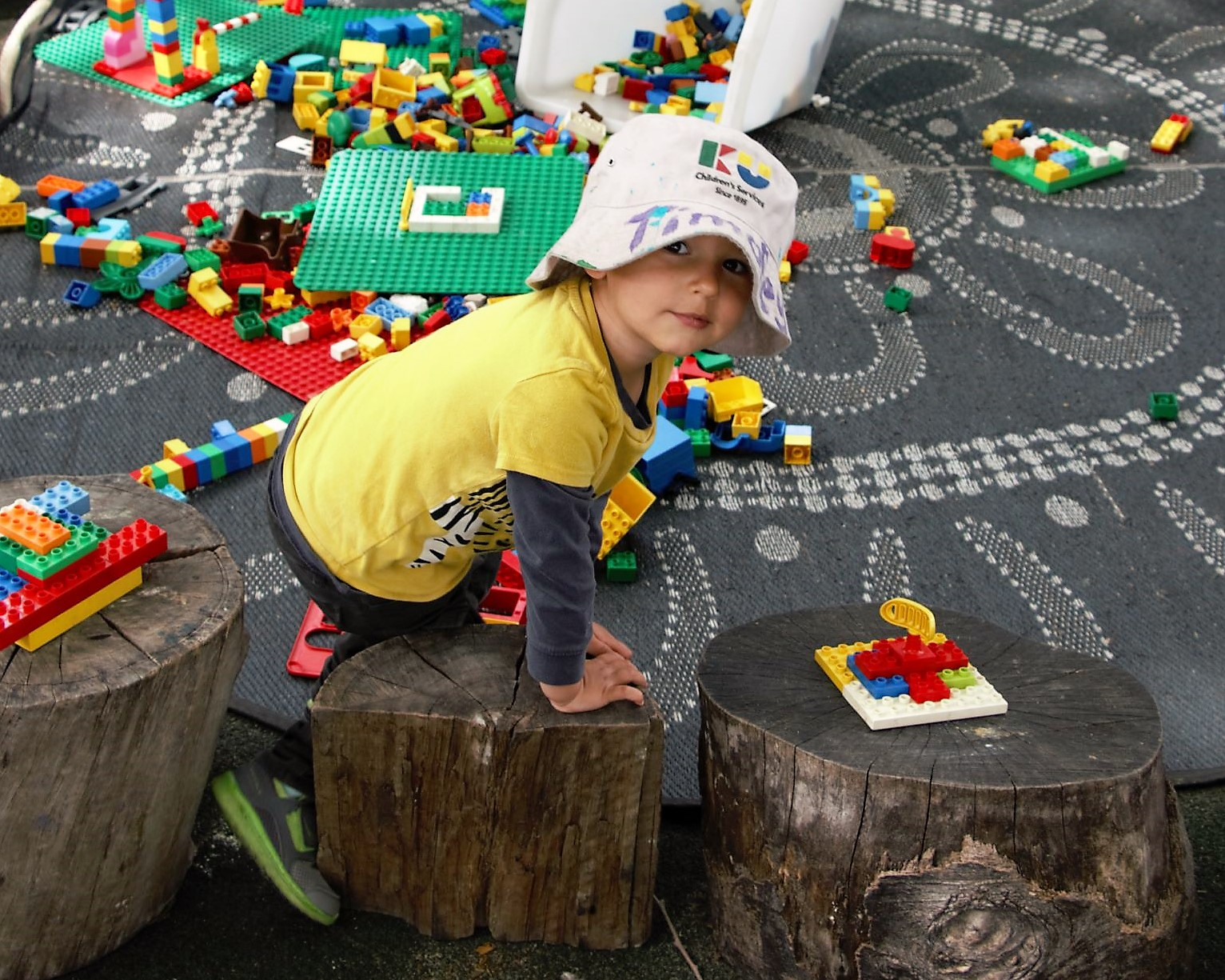 A boy playing with blocks at his child care in an outdoor environment