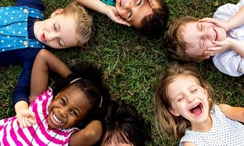 Children laying in a circle on the grass laughing and smiling