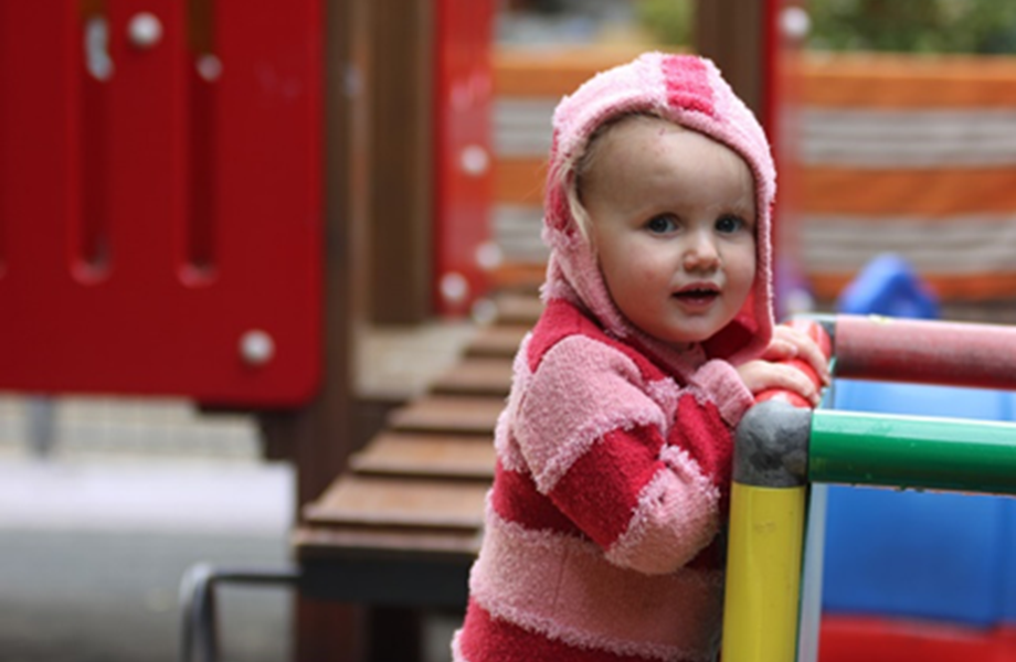 Toddler girl playing on play equipment