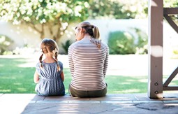 Mum and daughter talking while sitting at steps facing out towards a backyard
